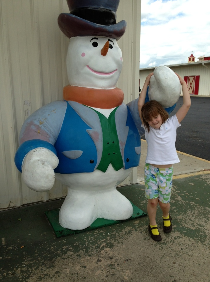 A getting her picture taken with a snowman in June.  Only in Ohio.