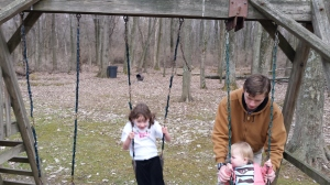 M being a nice big brother and pushing his sisters on the swings.